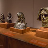 Rodin: Evolution of a Genius, exhibition of ~200 works of French sculptor Francois Auguste Rene Rodin (Auguste Rodin, 1840-1917), by Montreal Museum of Fine Arts & Musee Rodin in Paris, at Virginia Museum of Fine Arts November 21, 2015-March 13, 2016; includes plaster models, sketches, photos, bronze and marble pieces; photos allowed without flash - used 5D Mark III w/Canon 35/1.4 & UV filter; Rodin considered sketches heart of his work, with most sculpting in marble or casting in bronze done by others, under his supervision; here 4 works are displayed on a table, with a bust of Camille Claudel between 2 versions of Balzac head for full-figure statue (item at far end no known to me, nor did I check piece on wall); Monument to Balzac evolved through many phases 1891-98, caused outrage when unveiled 1898 & commission was cancelled; Musee Rodin notes say head had come to be a group of expressive elements more than a likeness of Balzac