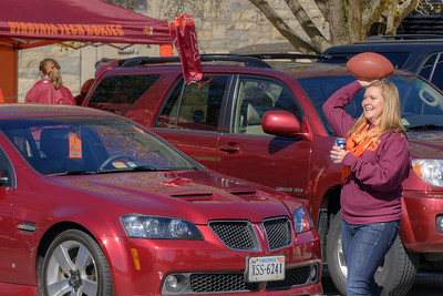 A woman holds balances a cold drink in one hand while throwing a football in the other at the Cassell Coliseum parking lot as the Virginia Tech University Hokies challenged the Duke University Blue Devils in football at Lane Stadium in Blacksburg, VA on Saturday, October 26, 2013. Copyright 2013 Jason Barnette