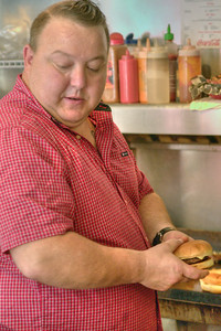 Owner Joe Deel prepares a burger at the Burger Bar in downtown Bristol, VA on Monday, October 14, 2013. Copyright 2013 Jason Barnette  The Burger Bar is locally-owned by Joe & Kayla Deel. The original restaurant in this building opened in 1942 under the name Snack King. Since that time, it has had several owners until Joe bought the restaurant from Ben Zandy and re-opened as The Burger Bar on January 1, 2013.