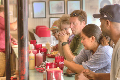 Customers enjoy lunch at the small bar at the Burger Bar in downtown Bristol, VA on Monday, October 14, 2013. Copyright 2013 Jason Barnette  The Burger Bar is locally-owned by Joe & Kayla Deel. The original restaurant in this building opened in 1942 under the name Snack King. Since that time, it has had several owners until Joe bought the restaurant from Ben Zandy and re-opened as The Burger Bar on January 1, 2013.
