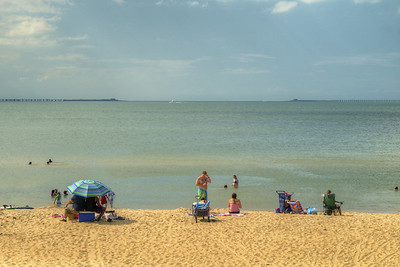 People enjoy the beach with a view of the Chesapeake Bay Bridge-Tunnel at First Landing State Park in Virginia Beach, VA on Wednesday, August 19, 2015. Copyright 2015 Jason Barnette