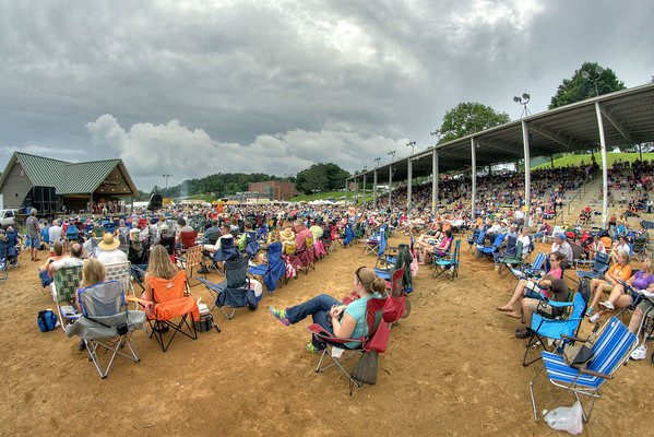 People sit under cloudy skies during musical performances at the 78th Annual Old Fiddlers' Convention in Galax, VA on Saturday, August 10, 2013. Copyright 2013 Jason Barnette