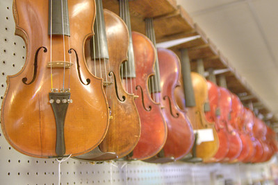 A long row of fiddles for sale at the historic Barr's Fiddle Shop on Main Street in Galax, VA on Saturday, August 10, 2013. Copyright 2013 Jason Barnette