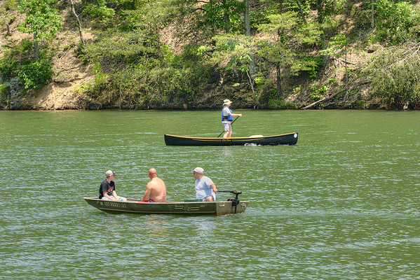 People with a small motor boat and a man canoe across the lake at Hungry Mother State Park in Marion, VA on Saturday, June 1, 2013. Copyright 2013 Jason Barnette