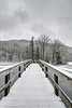 A long wooden footbridge crosses a frozen lake covered with snow to a small island with an ampitheater at Hungry Mother State Park in Marion, VA on Tuesday, January 21, 2014. Copyright 2014 Jason Barnette