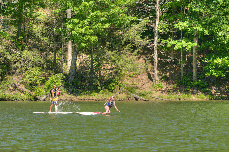 While a young couple play on paddleboards, one of them takes a fall into the lake at Hungry Mother State Park in Marion, VA on Saturday, May 24, 2014. Copyright 2014 Jason Barnette