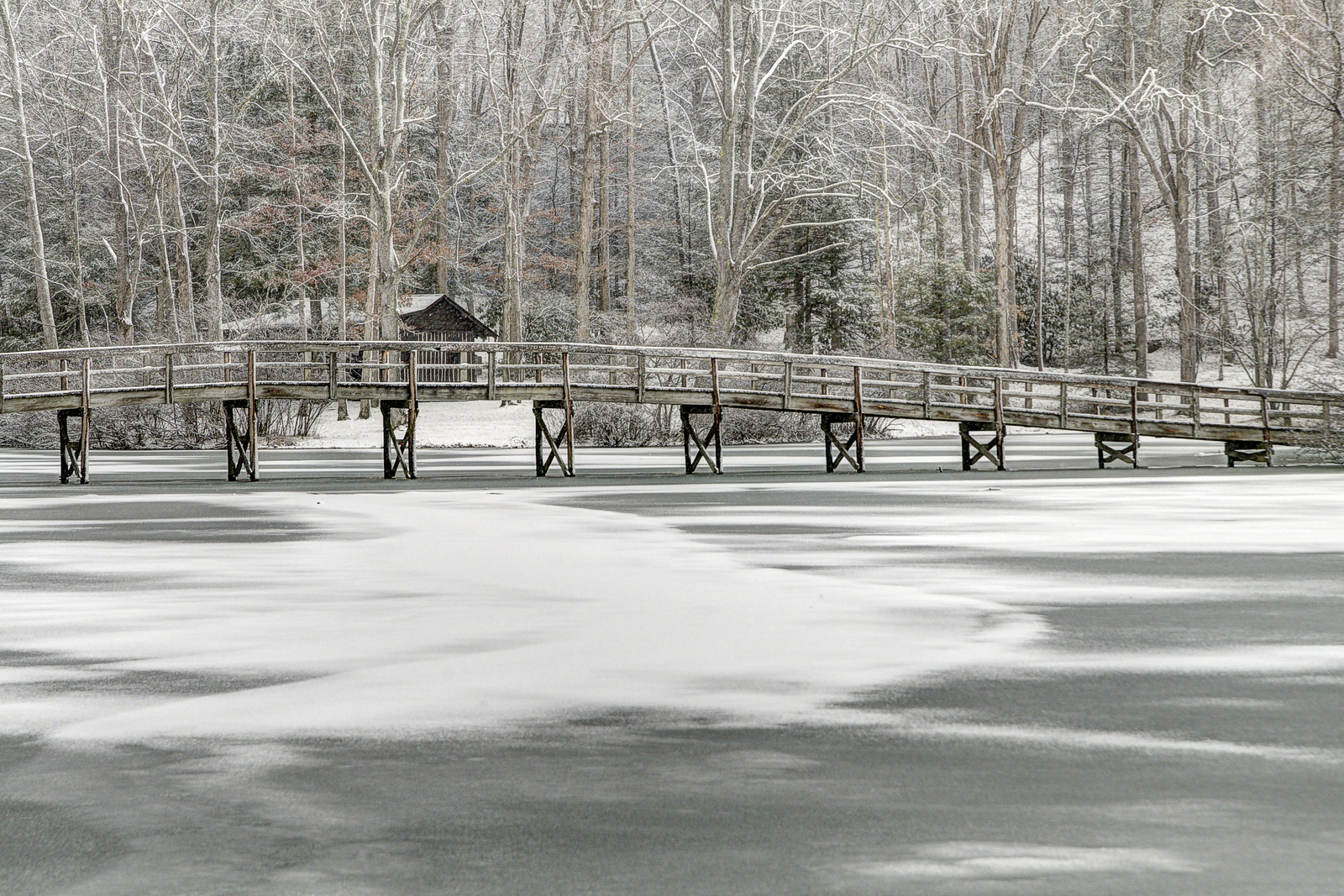 The wooden footbridge crosses a frozen lake covered with snow at Hungry Mother State Park in Marion, VA on Tuesday, January 21, 2014. Copyright 2014 Jason Barnette
