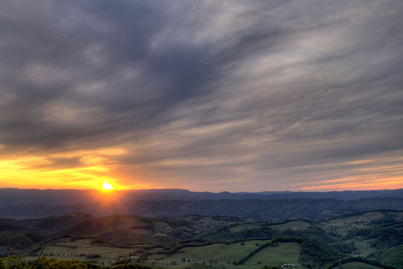 The sun peaks out from behind heavy clouds during sunset above a distant mountain range from a scenic overlook on Highway 16 in Marion, VA on Saturday, May 24, 2014. Copyright 2014 Jason Barnette