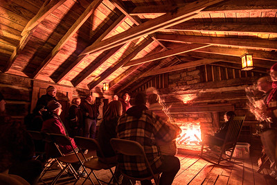 People huddle inside the Carter Cabin, watching a roaring fire and listening to stories from reenactors, during the Lighting of the Tunnel at Natural Tunnel State Park in Duffield, VA on Friday, December 13, 2013. Copyright 2013 Jason Barnette  The Lighting of the Tunnel is part of the annual 8 Days of Christmas event at Natural Tunnel State Park. The event includes thousands of lights from the main entrance to the top of the chair lift, rides on the chair lift to the bottom, lights decorating the walkways and tunnel, bonfires, marshmallows, music, and appearances by Santa Claus.