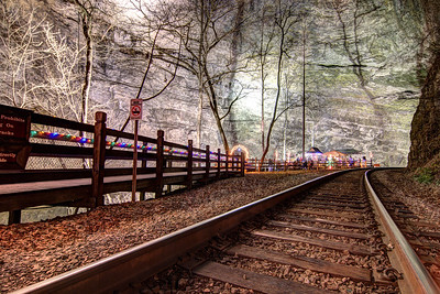 Holiday lights decorated the boardwalk leading across the railroad track during the Lighting of the Tunnel at Natural Tunnel State Park in Duffield, VA on Friday, December 13, 2013. Copyright 2013 Jason Barnette  The Lighting of the Tunnel is part of the annual 8 Days of Christmas event at Natural Tunnel State Park. The event includes thousands of lights from the main entrance to the top of the chair lift, rides on the chair lift to the bottom, lights decorating the walkways and tunnel, bonfires, marshmallows, music, and appearances by Santa Claus.
