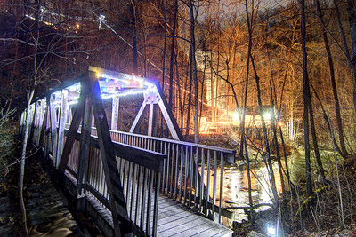 The wooden footbridge leading across the river to the Carter Cabin was decorated with holiday lights during the Lighting of the Tunnel at Natural Tunnel State Park in Duffield, VA on Friday, December 13, 2013. Copyright 2013 Jason Barnette  The Lighting of the Tunnel is part of the annual 8 Days of Christmas event at Natural Tunnel State Park. The event includes thousands of lights from the main entrance to the top of the chair lift, rides on the chair lift to the bottom, lights decorating the walkways and tunnel, bonfires, marshmallows, music, and appearances by Santa Claus.