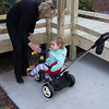 Anne helping Savannah on the tricycle
