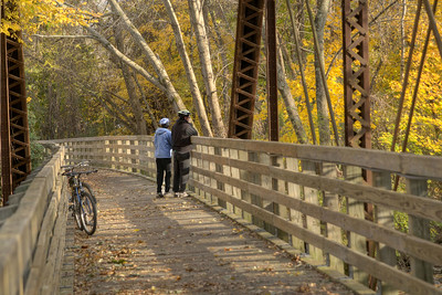 A couple take a break from bicycling to enjoy the beautiful fall colors from a trestle along the Virginia Creeper Trail, a 34-mile bicycling, jogging, and walking trail along an old railroad line from Abingdon through Damascus to White Top Mountain, in Damascus, VA on Saturday, November 2, 2013. Copyright 2013 Jason Barnette