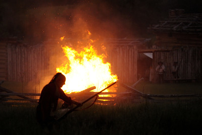 A Native American reenactor prepares to fire his rifle near a burning building during the night raid at the 15th Annual Raid at Martin's Station at Wilderness Road State Park in Ewing, VA on Saturday, May 9, 2015. Copyright 2015 Jason Barnette