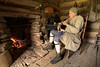 Reenactor Ebenezer Titus, captain of the militia posted inside Martin's Station, sits in front of a fire on a warm spring day at Wilderness Road State Park in Ewing, VA on Friday, May 24, 2013. Copyright 2013 Jason Barnette