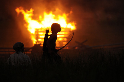 A young Native American reenactor with a bow runs past a burning building during the night raid at the 15th Annual Raid at Martin's Station at Wilderness Road State Park in Ewing, VA on Saturday, May 9, 2015. Copyright 2015 Jason Barnette