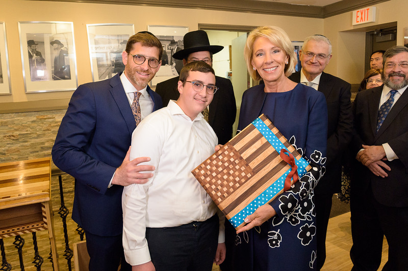 Secretary DeVos is presented with a handcrafted gift by Shimon Berger, a student of the Weiss Vocational Center at Yeshiva Darchei Torah as Rabbi Shimon Dachs, director (left); Rabbi Yaakov Bender (obscured); Mr. Ronald Lowinger and Rabbi Abba Cohen look on.