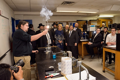 Secretary DeVos watches instructor Martin Hettrich performing an experiment at the Mesivta Chaim Shlomo science laboratory.