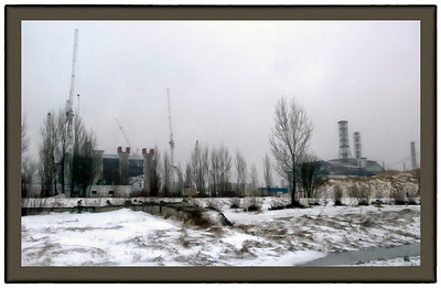 That's Chernobyl reactor 4, the ruined one, on the right. The New Safe Containment is the structure under construction on the left. It's an arch (as you can see through the trees) which will be jacked up in the air on legs one section at a time, until it's tall enough to slide on tracks over to the right to cover reactor 4. This photo from March, 2013.