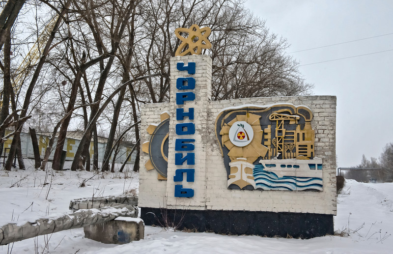 The Welcome Sign outside Chernobyl, Ukraine.   <font size=1>After the accident they installed new water pipes rather than use the old ones buried under irradiated ground. And instead of disturbing the soil, they laid them above ground. Note the pipe that crosses over the road, in the distance on the right.</font>
