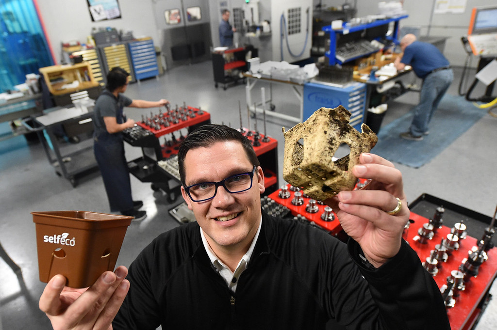 . Vista Tek owner Danny Mishek holds a new SelfEco pot, left, and a SelfEco pot pulled out of the ground after four weeks, right, showing the breakdown of material at the company\'s Stillwater manufacturing plant on Wednesday, Jan. 6, 2016. The mold-making and custom manufacturing company is launching a new line of biodegradable dinnerware and pots under the SelfEco label. Behind Mishek is the  mold-making division where the prototype mold was made for the SelfEco pot. (Pioneer Press: Jean Pieri)