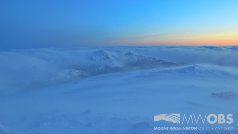 Sunrise (March 15, 2013) as clouds and blowing snow sweep past the peaks (Mt. Adams and Madison) to the north of Mount Washington.