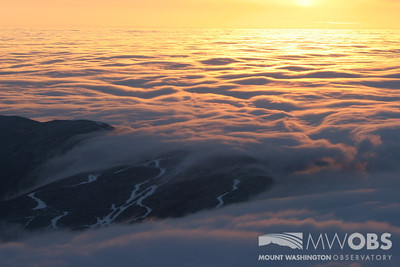 """A sea of clouds """"crashing"""" over Wildcat Ski Resort during a winter sunrise."""
