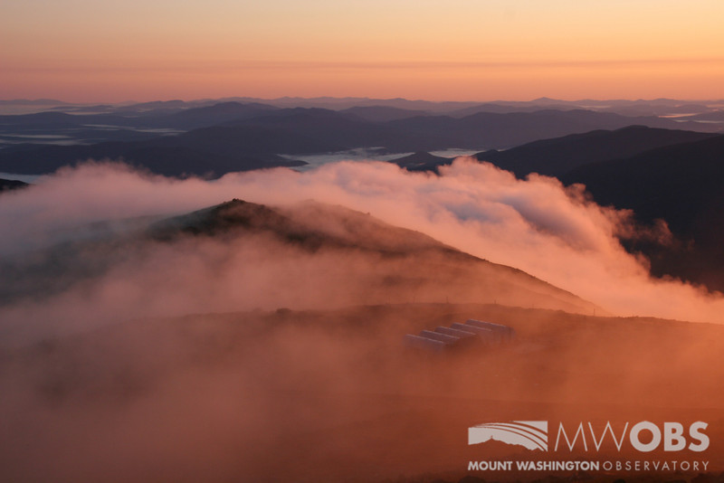 Clouds spilling over Ball Crag during a summer sunrise.