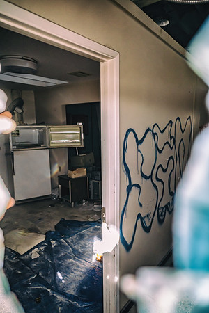 A refrigerator. A fan. Art on the walls. Plastic on the floors.