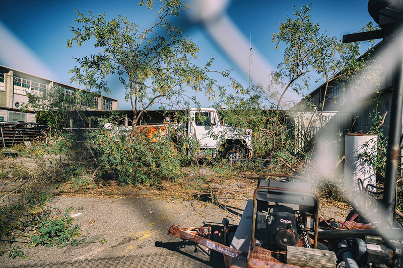 The fenced off yard of the transportation hub structures are home to overgrowth, two Marine Corps trucks, a generator, water heater and more.