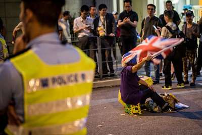 A woman waves a British flag while police look on during an event commemorating the 4th anniversary of the Umbrella Revolution in Hong Kong on September 28, 2018.