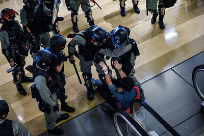 A man pleads for mercy after falling in front of riot police inside the Cityplaza Mall in Tai Koo Shing, Hong Kong. Local residents had  gathered peacefully in protest against an authoritarian government and an unaccountable police force. Riot police then stormed the mall, threatening civilians, and waving  weapons in their faces, The people would have none of it, though, shouting them out, holding their ground, and winning back their Sunday at the mall. November 3, 2019.