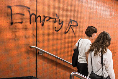 """Two subway ridres march past graffiti at one of the entrances to Tin Hau staiton in Hong Kong. A play on """"MTR"""", the subway corporation, """"EmptyR"""" has been one message used by protesters to express frustration with the transit agency's adoption as a base of operations for Hong Kong police. November 2, 2019."""