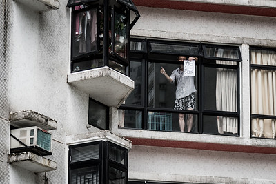 """A man stands in the window of his highise flat in the Kornhill neighbourhod of Hong Kong, offering a thumbs up and words of encouragement to residents below. The sign reads """"Ga Yao"""" which means """"add oil"""", a commonly used Cantonese metaphor  used to offer encouragement and support. August 17, 2019."""