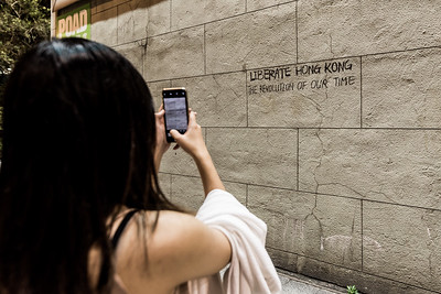 """A woman takes a photo of a recently added piece of graffiti in Central, Hong Kong. """"Liberate Hong Kong. Revolution of our time."""" has become a rallying cry during the many weeks of anti-government protests. August 16, 2019."""