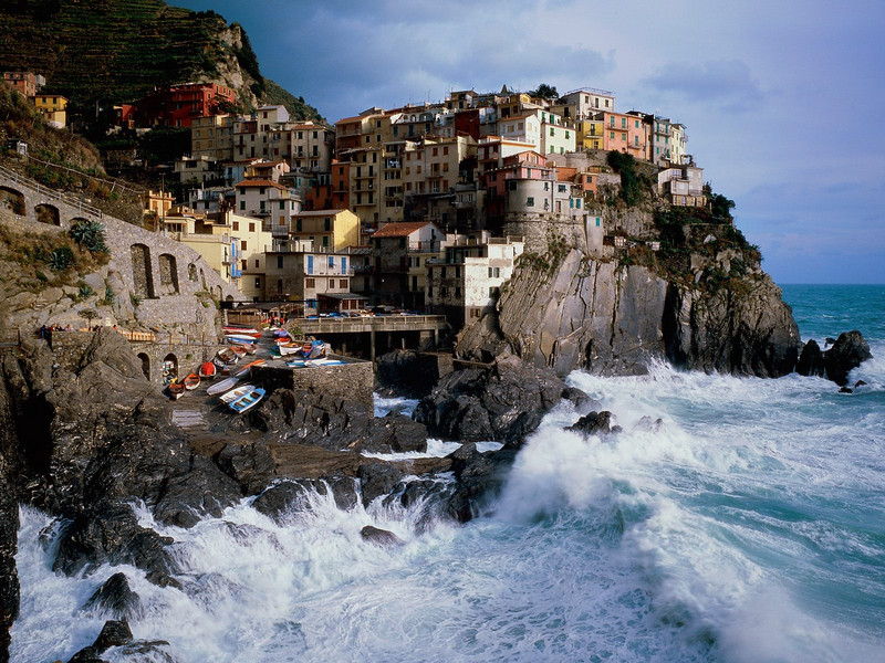 "The Cinque Terre is a rugged portion of coast on the Italian Riviera. It is in the Liguria region of Italy, to the west of the city of La Spezia. ""The Five Lands"" comprises five villages: Monterosso al Mare, Vernazza, Corniglia, Manarola, and Riomaggiore.  The coastline, the five villages, and the surrounding hillsides are all part of the Cinque Terre National Park and is a UNESCO World Heritage Site.  The Cinque Terre is noted for its beauty. Over centuries, people have carefully built terraces on the rugged, steep landscape right up to the cliffs that overlook the sea. Part of its charm is the lack of visible ""modern"" development. Paths, trains and boats connect the villages, and cars cannot reach it from the outside. It is a very popular tourist destination."
