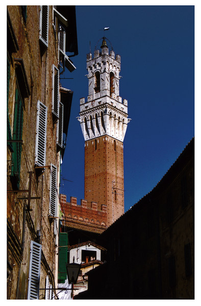 "The Torre del Mangia is a tower in Siena, in the Tuscany region of Italy. Built in 1325-1348, it is located in the Piazza del Campo, Siena's premier square, adiacent to the Palazzo Pubblico (Town Hall). When built it was one of the tallest secular towers in mediaeval Italy. At 102 m, it is now second only to Cremona's Torrazzo.  The name (meaning ""Tower of the Eater"") derives from its first guardian, Giovanni di Balduccio, nicknamed Mangiaguadagni for his tendency to spend all his money for food.  The upper part was realized by Agostino di Giovanni under design by one Mastro Lippo pittore, probably identifiable with Lippo Memmi.  The marble loggia, known as Cappella di Piazza, was added in 1352 as a vow for the Holy Virgin by the Sienese survivors from the Black Death. The pilaster were remade in the current form in 1378, the sculptures decorating them being executed in 1378-1382 by Mariano d'Angelo Romanelli e Bartolomeo di Tommé. The simple wooden ceiling once covering the loggia was replaced by the current Renaissance marble vault in 1461-1468 by Antonio Federighi, also author of the bizarre decorations of the coronation. In 1537-1539 Il Sodoma painted a fresco over the altar, now housed in the Town museum in the Palazzo Pubblico.  The clock was added in 1360.  The tower is visible from all parts of Siena and is adjacent to the Gothic Palazzo Pubblico.  The tower was built to be the exact same height as the Duomo di Siena as a sign that the church and the state had equal amounts of power.  The walls of the tower are approximatelty 11 ft. thick on each side. The stairwell up to the top of the tower is cramped and most visitors need to duck their heads at some point on the way up the tower. There is little room for two way traffic on the stairs, so only 25 visitors at a time are allowed to enter the tower."