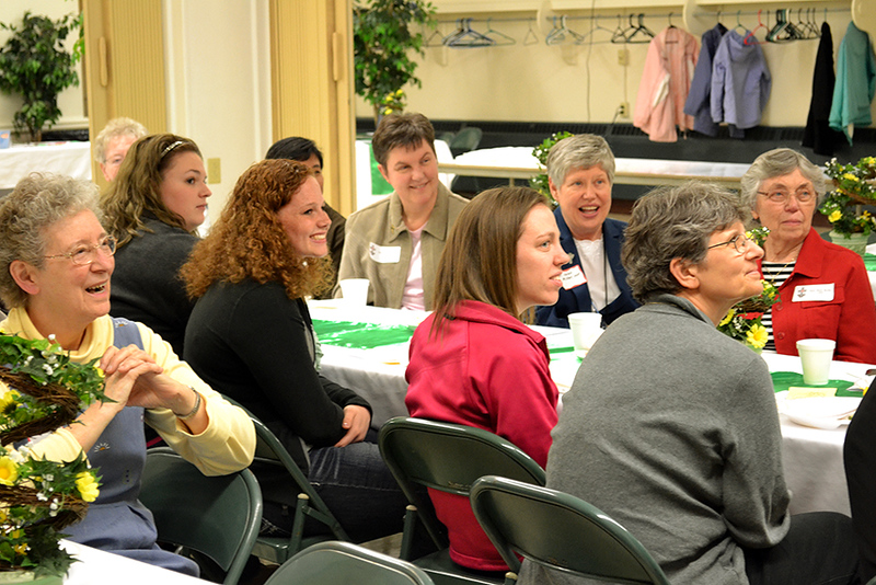 Single women and women religious listen to a speaker at a Martha Dinner April 8 at St. Denis Parish in Versailles.