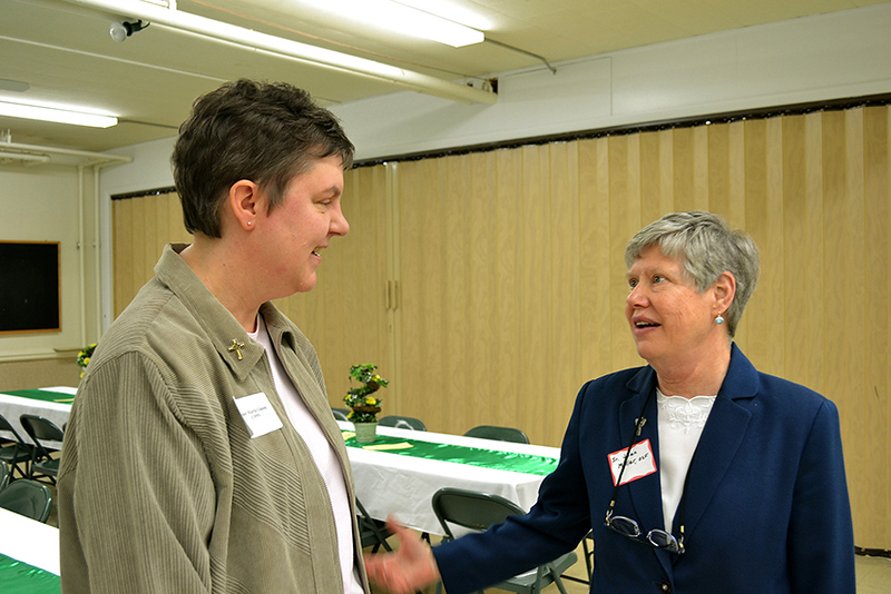 Precious Blood Sister Marla Gipson, left, talks with Oldenburg Franciscan Sister Joan Miller at a Martha Dinner April 8 in Versailles, Ohio.