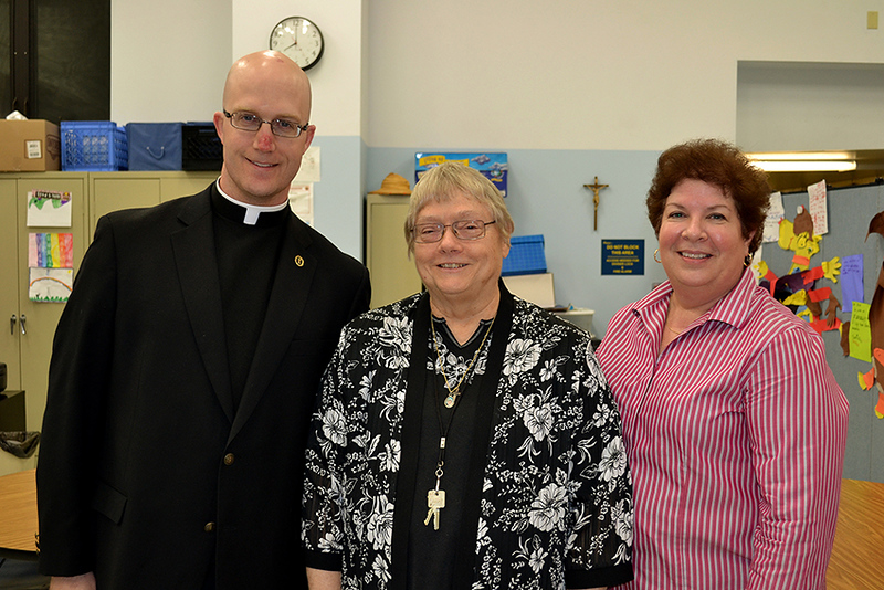 Father Kyle Schnippel, Precious Blood Sister Anne Schulz, center, and Dacia Daniels pose after a vocations event at Mother Teresa Catholic Elementary School.