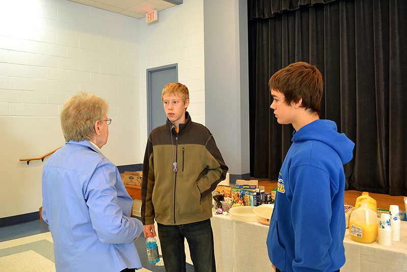 Sister Regina Albers talks to two young men at the 2012 'Stepping up the Call' pilgrimage at St. Charles Center.