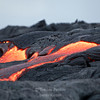Fresh lava breaks through the crust formed by earlier lava flows at the Kalapana lava fields, on the Big Island of Hawaii.