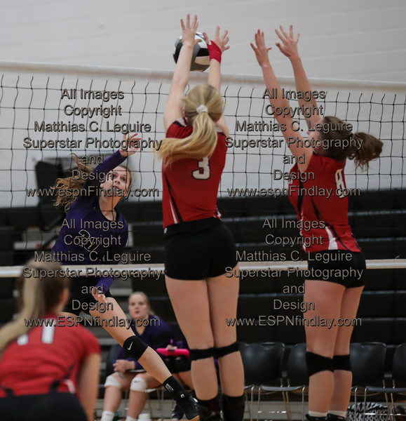 Arlington's Hailey Essinger (3) and Lindsay Dodds (8) block the spike from Ada's Josie Poling (20) for a point.