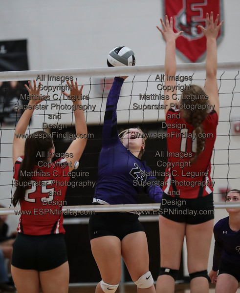 Ada's Kylie Acheson (23) spikes the ball over Arlington's Amber Durliat (25) and Abbie Sheets (18).