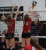 Arlington's Carlee Simon (11) and Abbie Sheets (18) get a piece of the spike from Ada's Kirsten Poling (2).