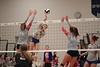 LB's Isabella Granger (13) records a kill spiking the ball between JM's Grace Slader (16) and Chloe Chard-peloquin (14).