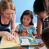 Volunteer helps girls with reading.
