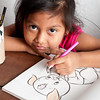 Girl draws in a coloring book.