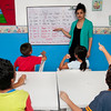 Volunteer teaches children English.