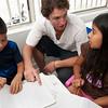 Volunteer helps children with their school homework.